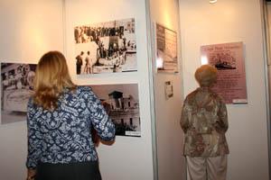 Asistentes a la inauguración ven las fotografías expuestas.