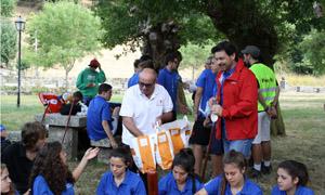 El presidente del Consello Regulador, Carlos Manuel Rodríguez, reparte bollos de pan entre los jóvenes, en compañía de Rodríguez Miranda.